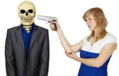 woman threatens with pistol to person - skeleton - stock photo