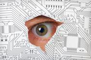 Eye looking through a hole in electronic circuit Stock Photos