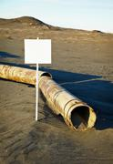 Sign near old rotting pipe - ecological disaster Stock Photos