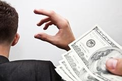 Stock Photo of dollars in the hands of a businessman