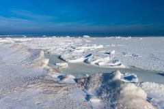 Frozen winter sea under snow during sunny day Stock Photos