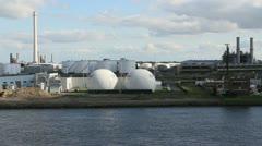 Netherlands Rotterdam refinery globe tanks reverse against stack Stock Footage