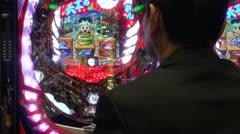 Japanese game addict behind electronic slot machine Stock Footage