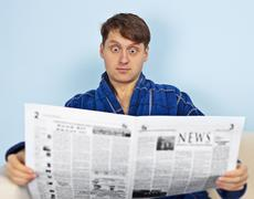Man reads a newspaper with a admiration Stock Photos