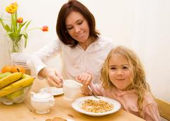 Mother and her daughter have a breakfast - stock photo