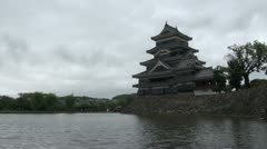 Time lapse of dark clouds flying over traditional castle in Japan Stock Footage