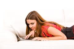 beautiful young woman using laptop on couch - stock photo