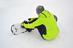 Stock Photo of sportsman with snowboard check binding on white snow