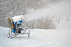 Snow gun (pulverizer) disperse artificial snow on mountain, winter details. Stock Photos