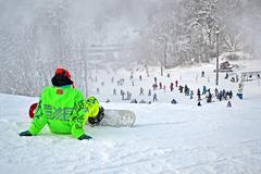Sportsman in green suite with snowboard seating on white snow Stock Photos