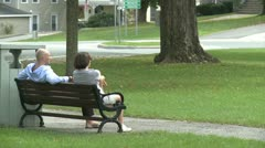 Conversing on a park bench (3 of 4) - stock footage