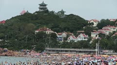 A lot of people at crowded bathing beach.China's Qingdao City.forest island. Stock Footage