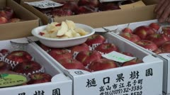 A woman moves a bucket of fresh apple parts at a local market in Japan Stock Footage