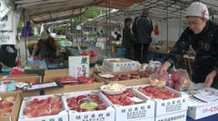 An elderly lady sets up her stall selling apples at a local Japanese market Stock Footage