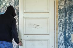 man opening door of decayed room - stock photo