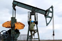 oil worker climbs to the pumpjack.JPG - stock photo