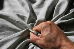 Grabbing bed sheet Stock Photos