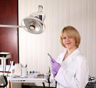 Female dentist with borer posing.JPG Stock Photos