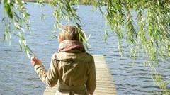 Woman walk wood lake bridge willow tree swan bird meet angry Stock Footage