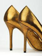 Pair of golden colored high heels Stock Photos