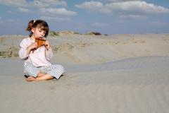 little girl play panpipe in desert.JPG - stock photo