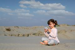 Little girl playing with tablet in desert.JPG Stock Photos