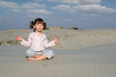 little girl meditating in desert.JPG - stock photo
