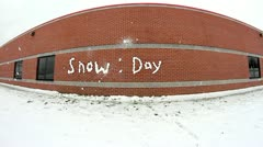 Snow day written with snow on school wall then snow balls thrown at it Stock Footage