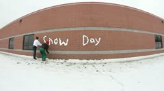 Two teenagers writing snow day on school wall and celebrating Stock Footage