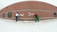 Cool time lapse of 2 girls writing snow day on school wall using snow Stock Footage