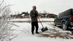 Man shoveling snow and then stops with chest pain / heart attack Stock Footage
