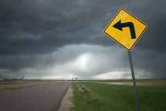 Road Sign with Left Turn Arrow and Ominous Storm Background - stock photo