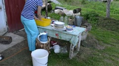 Deprived woman wash dirty dishes and cats walk. rural poverty Stock Footage