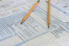 pencils on tax forms - stock photo