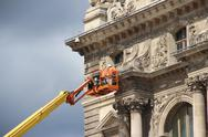 Stock Photo of workers maintain louvre museum facade