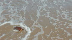 Brown bottle washed ashore by gentle waves Stock Footage