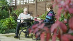 Mature couple of retirement age spend time together sitting in their garden Stock Footage