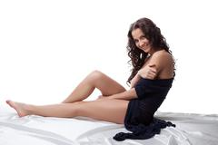 sexy young woman in cardigan lying on white sheet - stock photo