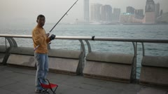 Old asian man amateur fishing victoria harbour hong kong Stock Footage