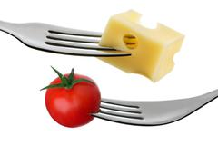 Tomato and cheese on a fork against white background Stock Photos
