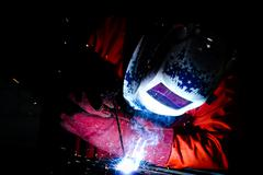 welder welding metal in industrial zone - stock photo