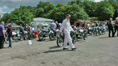 Marshall in overalls walks in front of vintage motorcycles Stock Footage