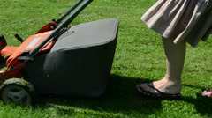 Woman girl skirt flip-flop shoes mow lawn grass cutter in yard Stock Footage