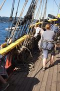 the crew sets the sails of the lady washington - stock photo