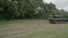 Army tank driving in a field Stock Footage