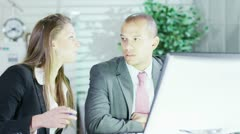 Male and female office workers discuss the project they are working on Stock Footage