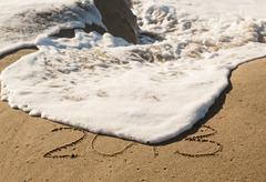 2013 in sand being covered by sea waves - stock photo