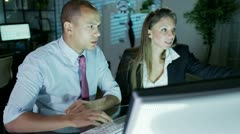 Businessman and businesswoman working late at night in a room full of computers Stock Footage