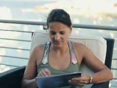 Happy woman with tablet computer sitting on the terrace, crane shot Stock Footage