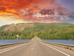 beautiful road on the lake with sunset colors - stock photo